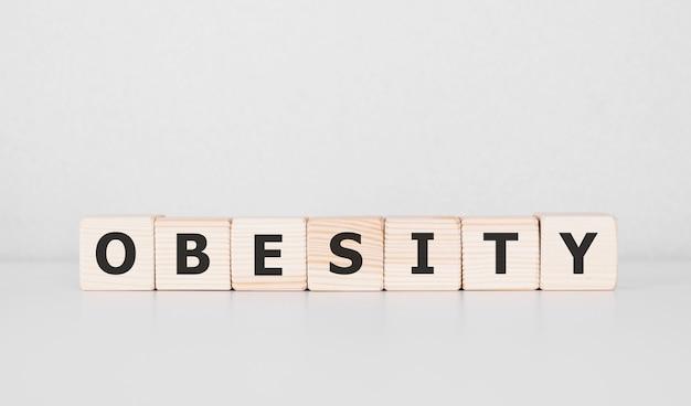 Wort fettleibigkeit geschrieben auf holzblock. unternehmenskonzept