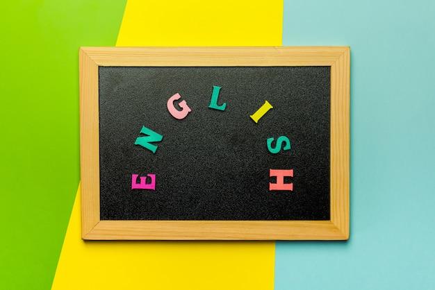 Wort lernen englisch gemacht mit holzbuchstaben über dem holzbrett