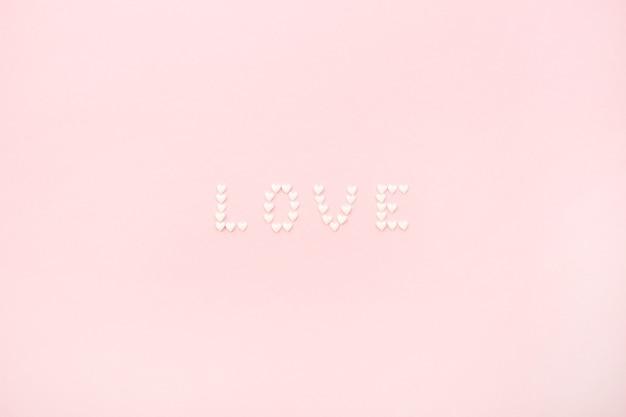 Wort liebe aus herzen auf blassrosa hintergrund. flache lage, ansicht von oben liebeskonzept.