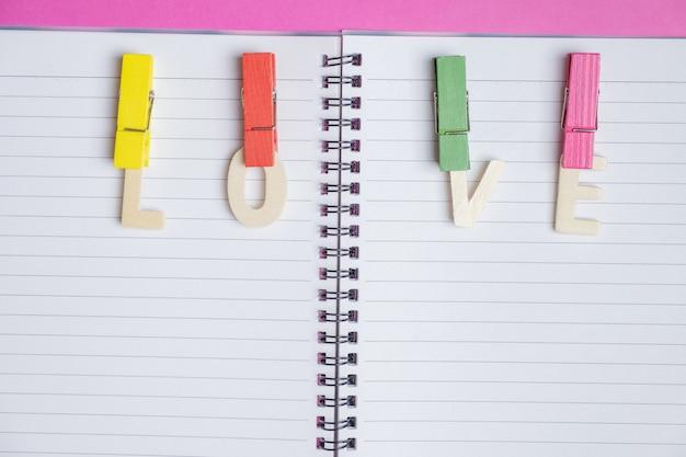 Wort liebe im leeren buch auf rosa hintergrund mit platz für text