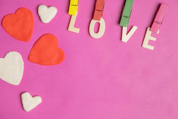 Wort liebe in den roten herzen auf rosa hintergrund, liebesikone, valentinstag, beziehungskonzept