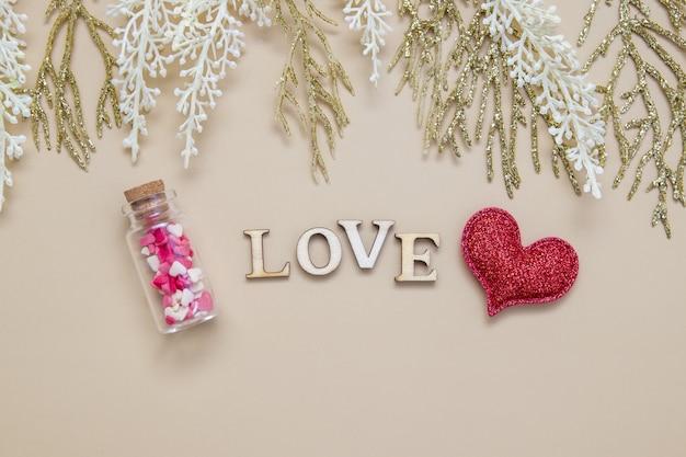 Wort lieben holzbuchstaben mit rotem herzen und zweigen
