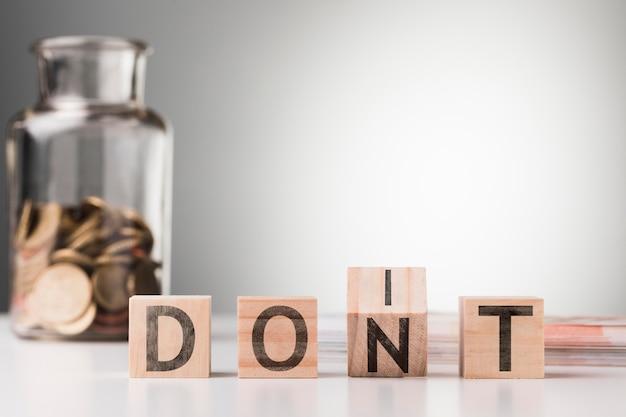 Wort nicht neben glas mit münzen auf dem tisch
