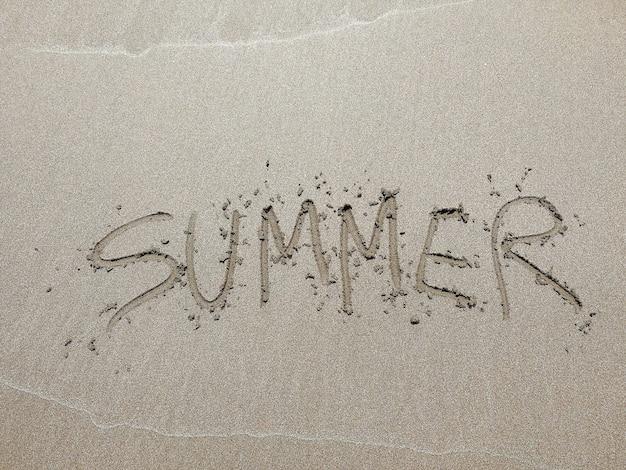 Wort sommer geschrieben an einem sandstrand - urlaubskonzept hintergrund