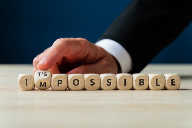 Wort unmöglich geschrieben auf holzwürfeln mit männlichem finger, der den buchstaben m umdreht, um es zu einem möglichen zeichen zu machen.