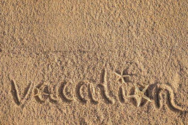 Wort urlaub am strand in den sand geschrieben