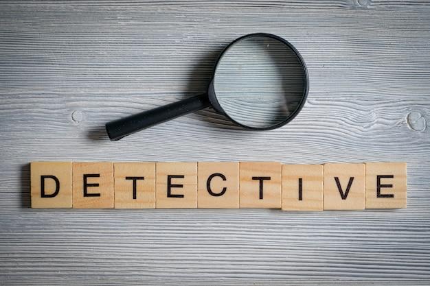 Wort von hölzernen buchstaben - detektiv, auf einem grau mit einem glasvergrößerungsglas. untersuchungsberuf.