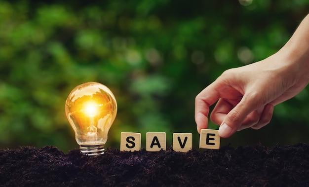 Wort von save auf holzwürfeln mit glühbirne mit handkonzeptidee, die energie spart glühbirne
