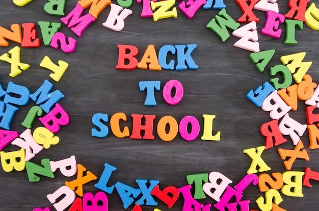 Wort zurück zur schule zusammengesetzt aus farbigen buchstaben auf einem schwarzen hölzernen hintergrund