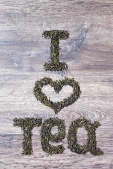 Worte ich liebe dich aus grünen teeblättern auf holzhintergrund