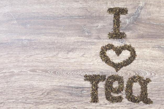 Worte ich liebe tee aus grünen teeblättern auf holzhintergrund. text rechts