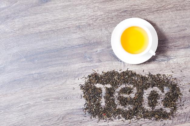 Worte ich liebe tee aus grünen teeblättern auf holzhintergrund.