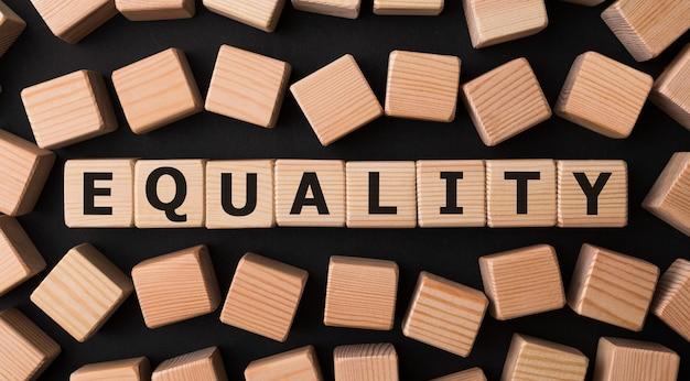 Wortgleichheit geschrieben auf holzblock Premium Fotos