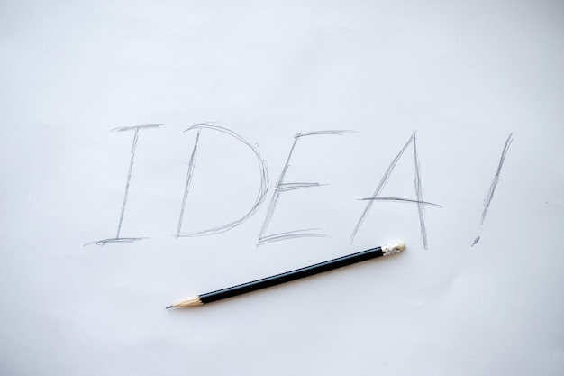 Wortidee. kreatives konzept. holzbuchstaben des idea-wortes mit handgeschriebenem akronym, bleistiftfoto isoliert auf weißem papier und interaktiv