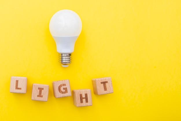 Wortlicht und glühbirne auf gelbem hintergrund, konzeptbild, layout mit platz für text, draufsicht