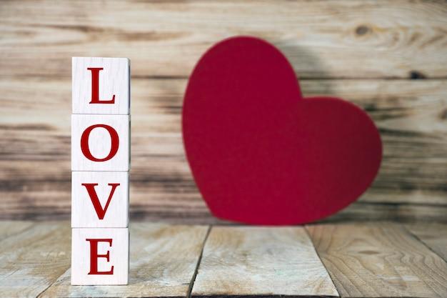 Wortliebe aus holzwürfelblöcken und großem roten herzen auf holzbrett. grußkarte zum valentinstag