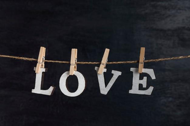 Wortliebe von holzbuchstaben mit wäscheklammern auf schwarzer oberfläche