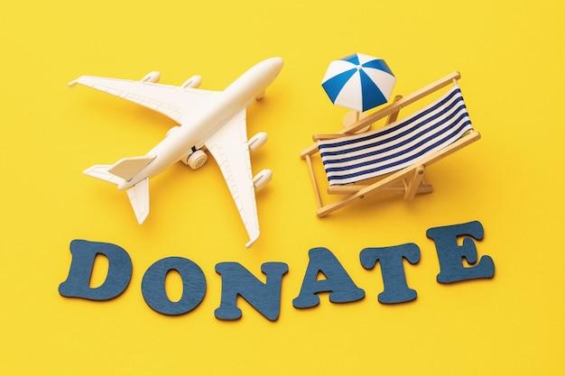 Wortspielzeugflugzeug sonnenschirm und liegestuhl auf gelbem hintergrund urlaubsspendenkonzept