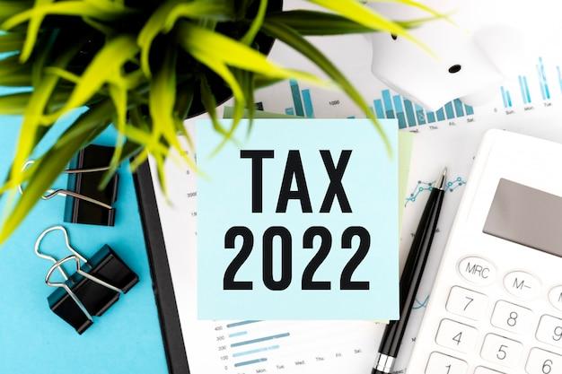 Wortsteuer 2022 auf aufkleber. rechner, schweinchen und stift. geschäfts- und steuerkonzept auf weißem hintergrund. ansicht von oben.