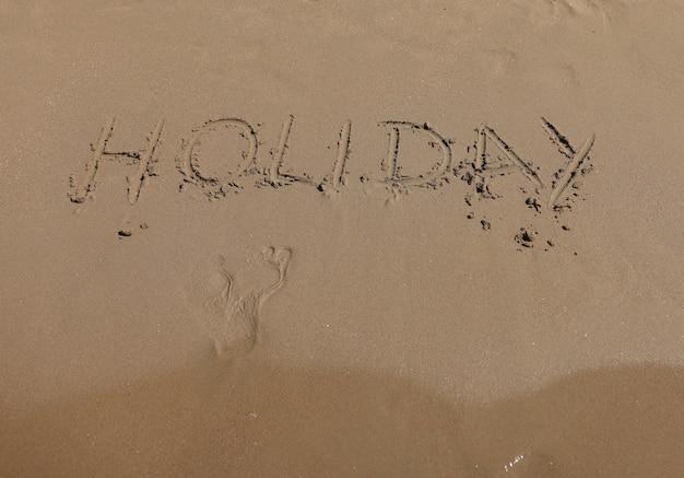Worturlaub und fußabdrücke schreiben auf sand. küste aus weichem sand und meereswellen.