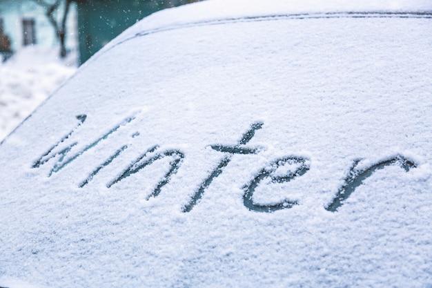 Wortwinter auf dem gefrorenen glas einer auto-windschutzscheibe.