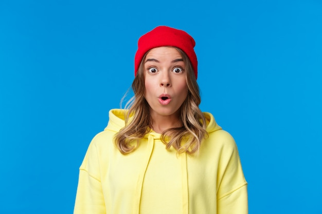 Wow, erzähl mir mehr. fasziniertes und neugieriges blondes europäisches mädchen, das erstaunt starrt, beeindruckt nach luft schnappt, etwas aufregendes sieht, interessante neuigkeiten hört und in roter mütze und gelbem hoodie steht