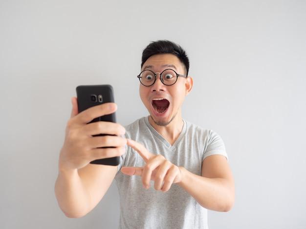 Wow gesicht des mannes schockiert, was er auf dem smartphone sieht.
