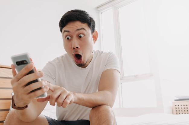 Wow gesicht des mannes überrascht beim blick auf das smartphone in seiner wohnung