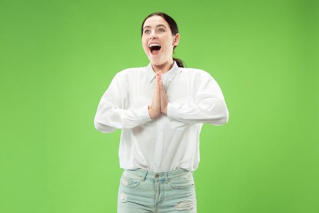 Wow. schönes weibliches halblanges vorderes porträt lokalisiert auf grünem studiohintergrund. junge emotionale überraschte frau, die mit offenem mund steht. menschliche emotionen, gesichtsausdruckkonzept. trendige farben
