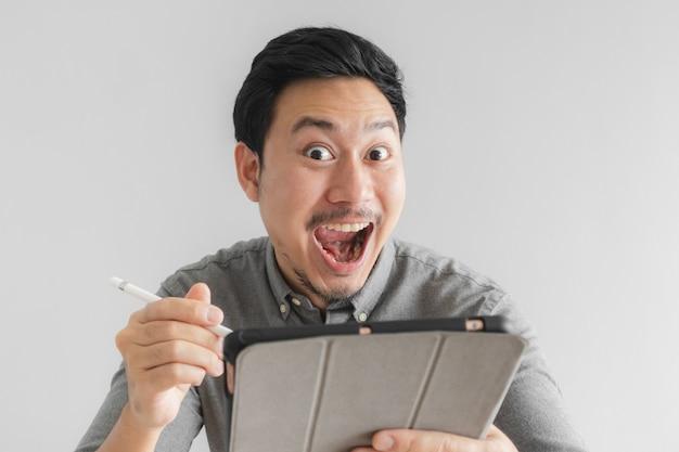Wow und überraschte unternehmergeschäftsmannarbeit an seiner tablette mit grauem hintergrund.