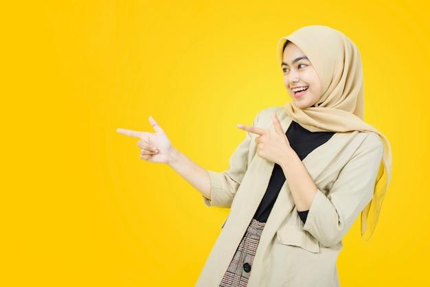 Wow und überraschtes gesicht der asiatischen frau mit hand zeigen auf gelbe wand