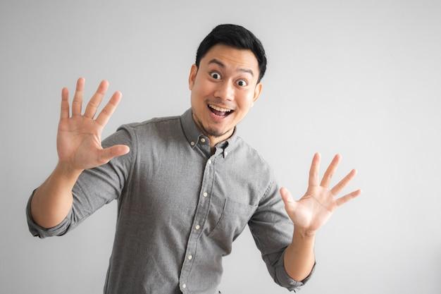 Wow und überraschtes gesicht des lustigen schönen mannes mit dem handzeichenzeigen.