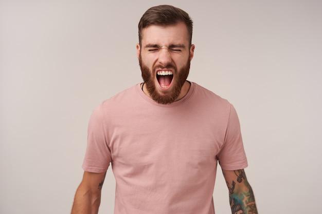 Wroth brünette bärtige kerl mit tätowierungen, die wütend mit weit geöffnetem mund schreien und sein gesicht stirnrunzeln, die augen geschlossen halten, während sie in freizeitkleidung auf weiß stehen