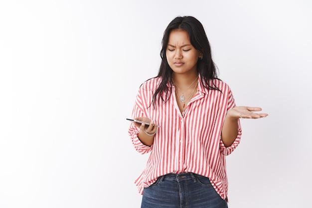 Wtf soll es bedeuten. porträt einer verwirrten und frustrierten jungen freundin, die fragend achselzuckend und stirnrunzelnd steht, während sie das smartphone hält und eine seltsame nachricht im handy über weißer wand liest