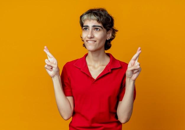 Wünschendes junges kaukasisches mädchen mit pixie-haarschnitt, der gekreuzte fingergeste tut, die gerade lokalisiert auf orange hintergrund mit kopienraum schaut