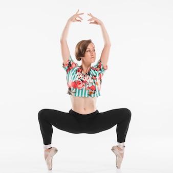 Würdevolle ballerina, die gegen weißen hintergrund aufwirft