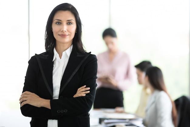 Würdevolle geschäftsfrau im schwarzen anzug, der mit würdiger weise im büro steht