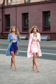Würdevolle geschäftsfrauen in den eleganten kleidern gehend in stadt