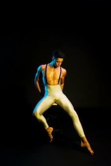 Würdevoller männlicher ballettausführender, der im scheinwerferlicht sitzt