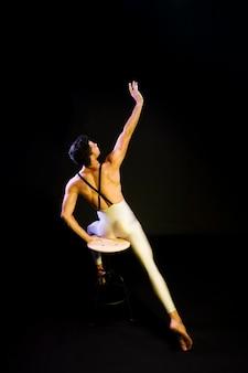 Würdevoller männlicher balletttänzer, der in scheinwerfer ausdehnt
