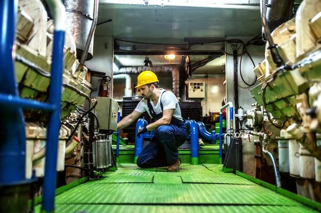 Würdiger kaukasischer mechaniker in overalls und mit helm, der im schiff kniet und den motor repariert.