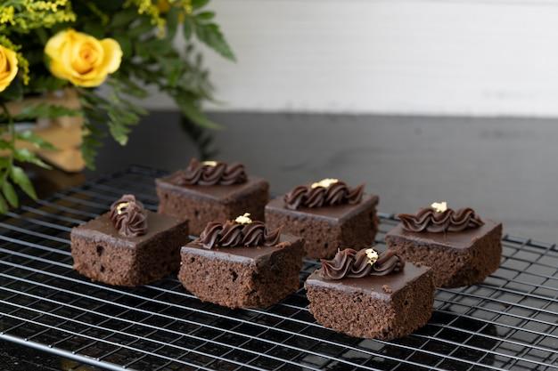 Würfel aus frisch zubereiteten schokoladenbrownies, verziert mit essbarem goldpapier auf einem kühlregal.