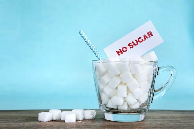 Würfel des raffinierten zuckers im glas und im ungesunden nahrungsmittelkonzept des keinen zucker-tagaufklebers
