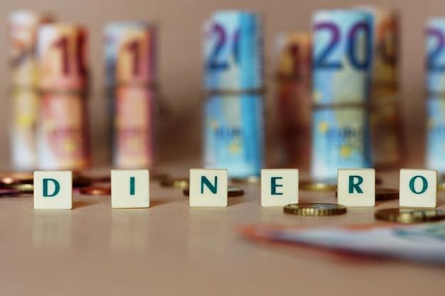 Würfel, die dinero vor spanischen dinero-scheinen und münzen auf dem tisch buchstabieren