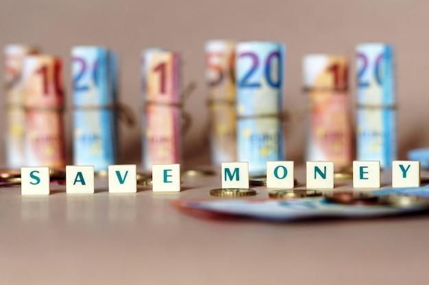 Würfel mit der aufschrift save money auf dem tisch mit spanischen dinero-scheinen und -münzen