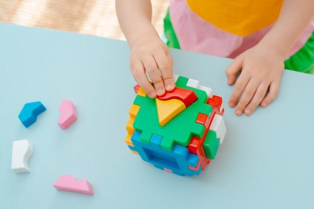 Würfel mit eingefügten geometrischen formen aus farbigen kunststoffblöcken
