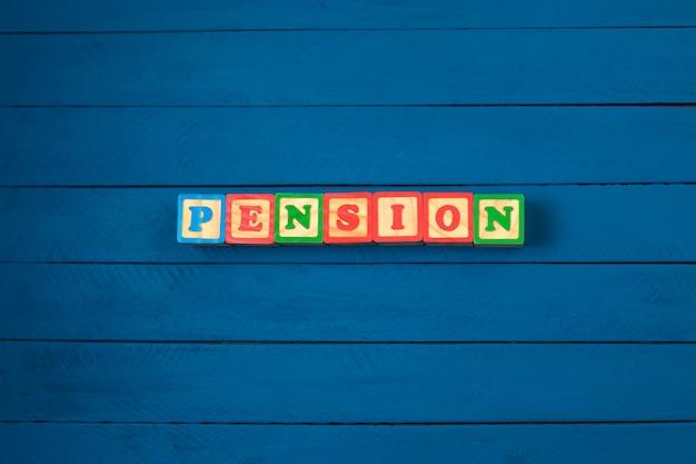 Würfel mit wort pension auf blauem hölzernem hintergrund.