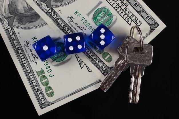 Würfel und hundert-dollar-scheine mit hausschlüsseln auf schwarzer oberfläche. alles steht auf dem spiel. glücksspiel. viel glück, glück.