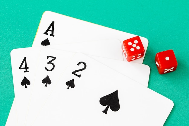 Würfel und karten auf grünem kasinotisch