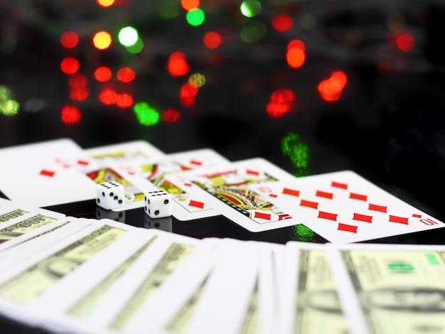 Würfel und spielkarten – das königliche fleisch des pokers. auf rückseitigem hintergrund - casinolichter.